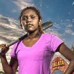 Young lady wearing a pink top holding a baseball bat in front of the Yalata boomerang